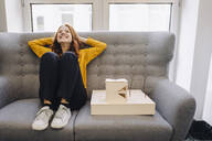 Happy woman sitting on couch next to architectural model - KNSF06652
