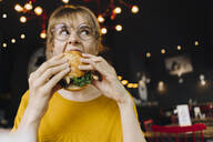Young woman eating burger in a restaurant - KNSF06661