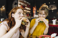 Two female friends eating burger in a restaurant - KNSF06664