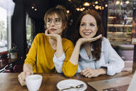 Two female friends with laptop in a cafe - KNSF06667