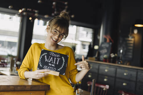 Young woman in a restaurant holding 'wait to be seated' sign - KNSF06670