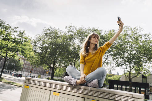 Young woman sitting on a box in the city taking a selfie - KNSF06673