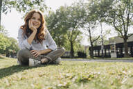 Smiling redheaded woman sitting on grass verge - KNSF06676