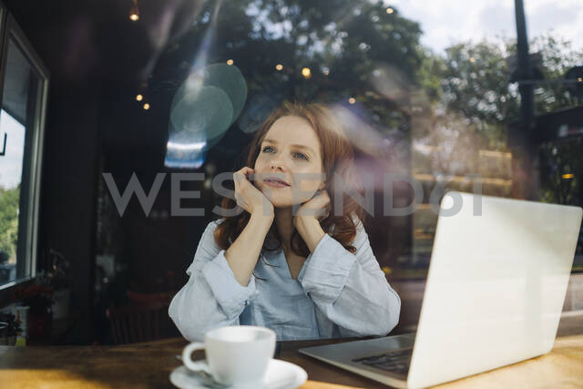 Redheaded woman with laptop in a cafe thinking - KNSF06679 - Kniel Synnatzschke/Westend61