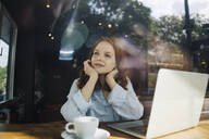 Redheaded woman with laptop in a cafe thinking - KNSF06679