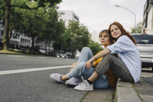 Female friends sitting at the roadside in the city - KNSF06688
