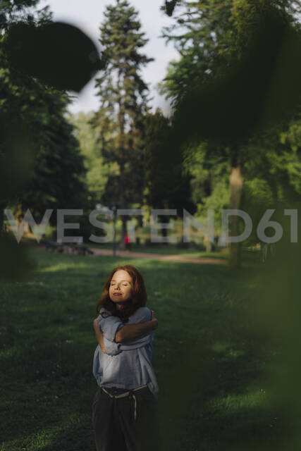 Redheaded woman in a park hugging herself - KNSF06703 - Kniel Synnatzschke/Westend61