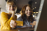 Two happy female friends with laptop and credit card in a cafe - KNSF06709