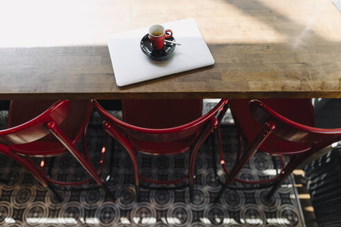 Laptop and cup of coffee on table in a cafe - KNSF06715