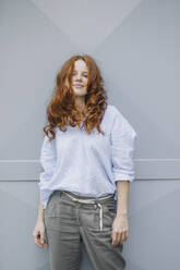 Portrait of beautiful redheaded woman standing at a wall - KNSF06718