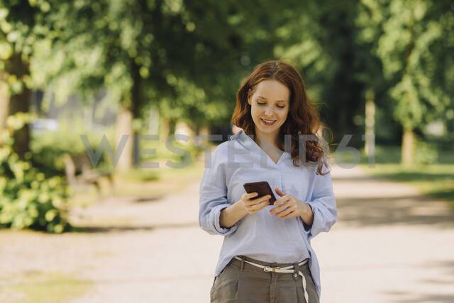 Smiling redheaded woman using cell phone in park - KNSF06727 - Kniel Synnatzschke/Westend61