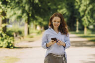 Smiling redheaded woman using cell phone in park - KNSF06727