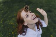 Redheaded woman balancing a pine cone on her forehead - KNSF06730