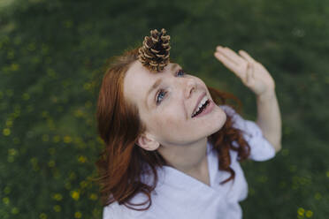 Redheaded woman balancing a pine cone on her forehead - KNSF06730