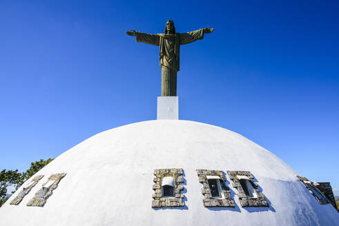 Low angle view of Christ the Redeemer Statue against clear blue sky during sunny day, Puerto Plata, Dominican Republic - RUNF03295