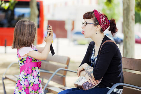 Little girl taking photo of her mother with smartphone - XCF00245