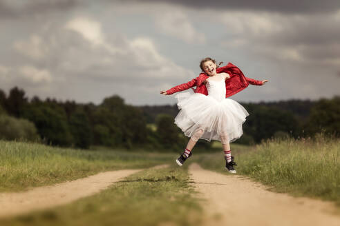Portrait of happy girl wearing red leather jacket and tutu jumping in the air on dirt track - STBF00413