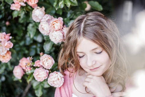 Portrait of girl with eyes closed beside pink rosebush - STBF00419