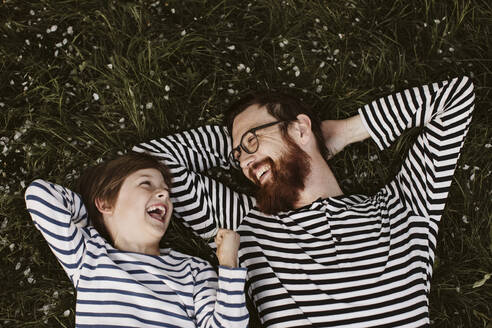 Father and son wearing similar stripped shirts lying on grass - JOHF01226