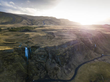 Iceland, Aerial view of waterfall splashing down high cliff at sunset - DAMF00077