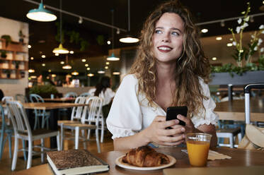 Smiling young woman with smartphone in a cafe having breakfast - IGGF01333