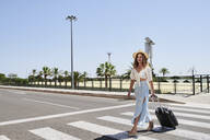 Young woman with baggage crossing a street at the airport - IGGF01339