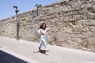 Happy young woman running along a wall - IGGF01351