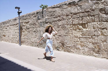 Happy young woman running along a wall - IGGF01351