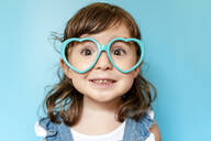 Portrait of cute little girl with heart shaped glasses on blue background - GEMF03177