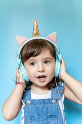 Portrait of cute little girl listening music and singing with unicorn shaped earphones on blue background - GEMF03180