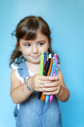 Portrait of cute little girl picking up a handful of colored ballpoint pens on blue background - GEMF03186