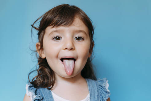 Portrait of cute little girl with tongue out on blue background - GEMF03189
