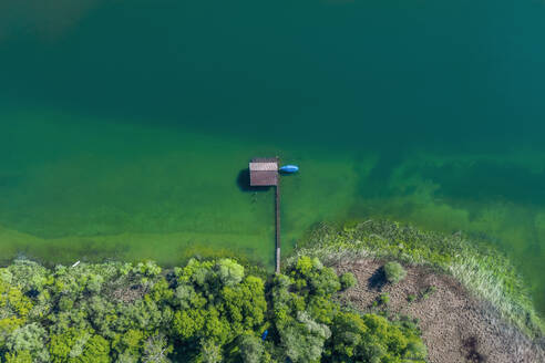 Germany, Bavaria, Aerial view of boathouse standing on green shore of Chiemsee lake - MMAF01144
