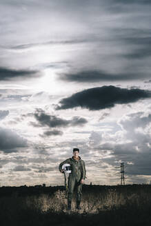 Man posing dressed as an astronaut on a meadow with dramatic clouds in the background - DAMF00081