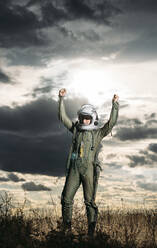 Man posing dressed as an astronaut on a meadow with dramatic clouds in the background - DAMF00084
