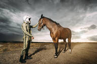 Man dressed as an astronaut with a horse on a meadow with dramatic clouds in the background - DAMF00087