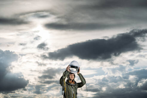 Man posing dressed as an astronaut on a meadow with dramatic clouds in the background - DAMF00093