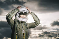 Man posing dressed as an astronaut with dramatic clouds in the background - DAMF00096