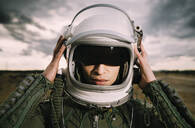 Man with astronaut helmet, dramatic clouds in the background - DAMF00099