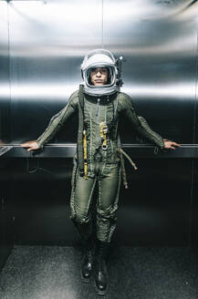 Man posing dressed as an astronaut in skyrocket elevator - DAMF00105