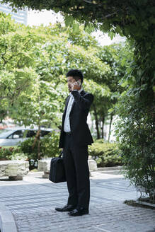 Young businessman talking on the phone in the city - JPIF00167