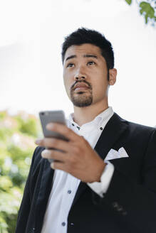 Young businessman holding cell phone outdoors - JPIF00170