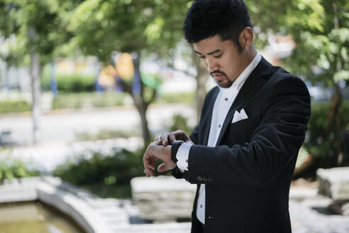 Young businessman in the city checking the time - JPIF00173