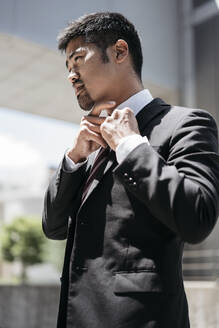 Young businessman in the city adjusting his tie - JPIF00176