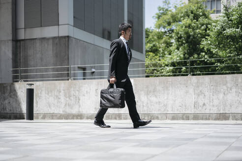 Young businessman walking in the city - JPIF00179