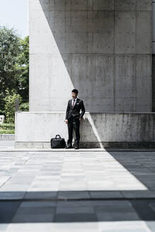 Young businessman standing at concrete wall in the city - JPIF00182
