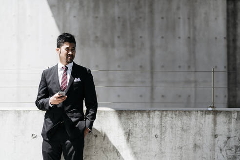 Young businessman standing at concrete wall in the city - JPIF00185