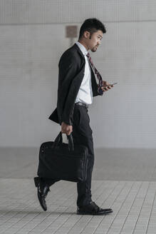 Young businessman with cell phone walking in the city - JPIF00191