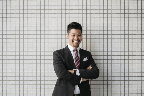 Portrait of happy young businessman at tiled wall - JPIF00194