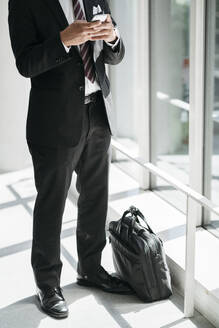 Low section of businessman using cell phone at the window - JPIF00203